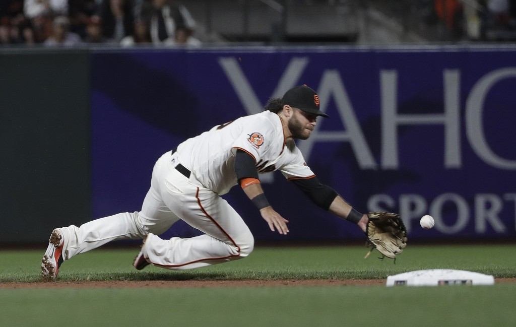San Francisco Giants shortstop Brandon Crawford fields a base hit by Pittsburgh Pirates' Elias Diaz during the ninth inning of a baseball game in San