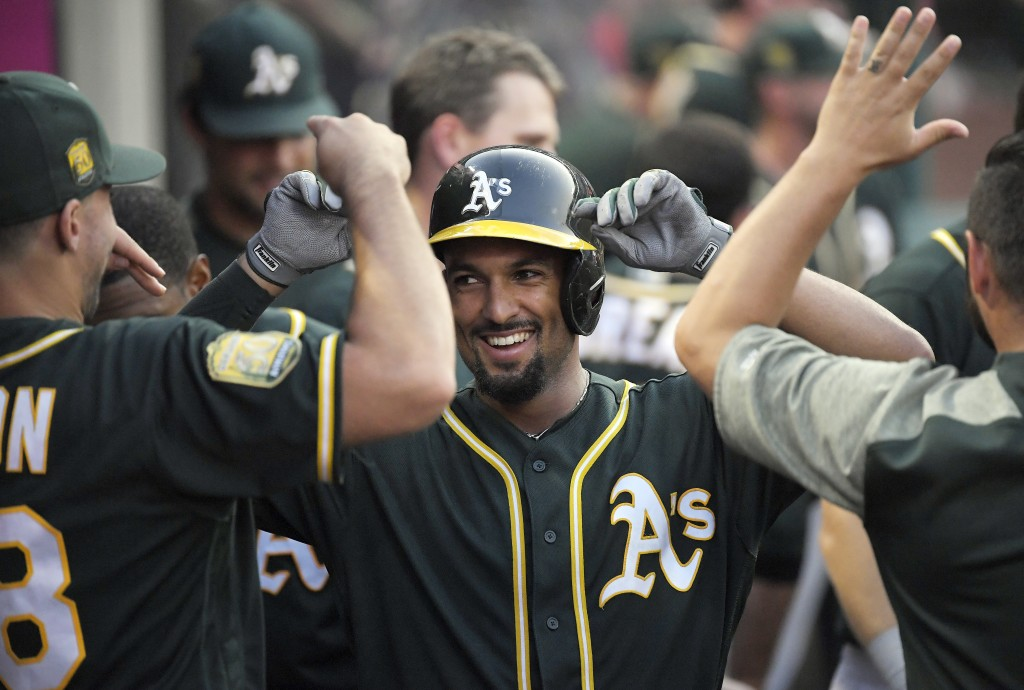 Oakland Athletics' Marcus Semien, center, is congratulated by teammates after hitting a solo home run during the fourth inning of a baseball game agai