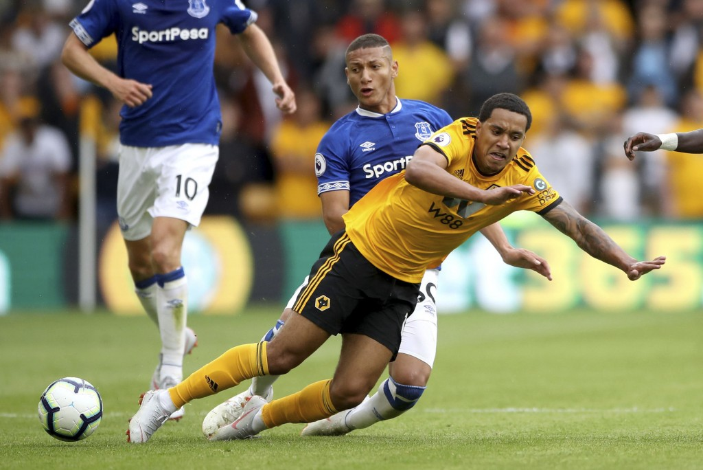 Everton's Richarlison, back, tackles Wolverhampton Wanderers' Helder Costa during their English Premier League soccer match at Molineux in Wolverhampt