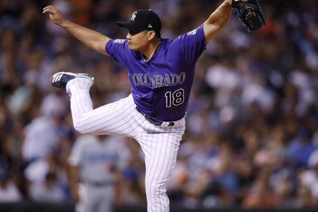 Colorado Rockies relief pitcher Seunghwan Oh works against the Los Angeles Dodgers in the eighth inning of a baseball game Saturday, Aug. 11, 2018, in