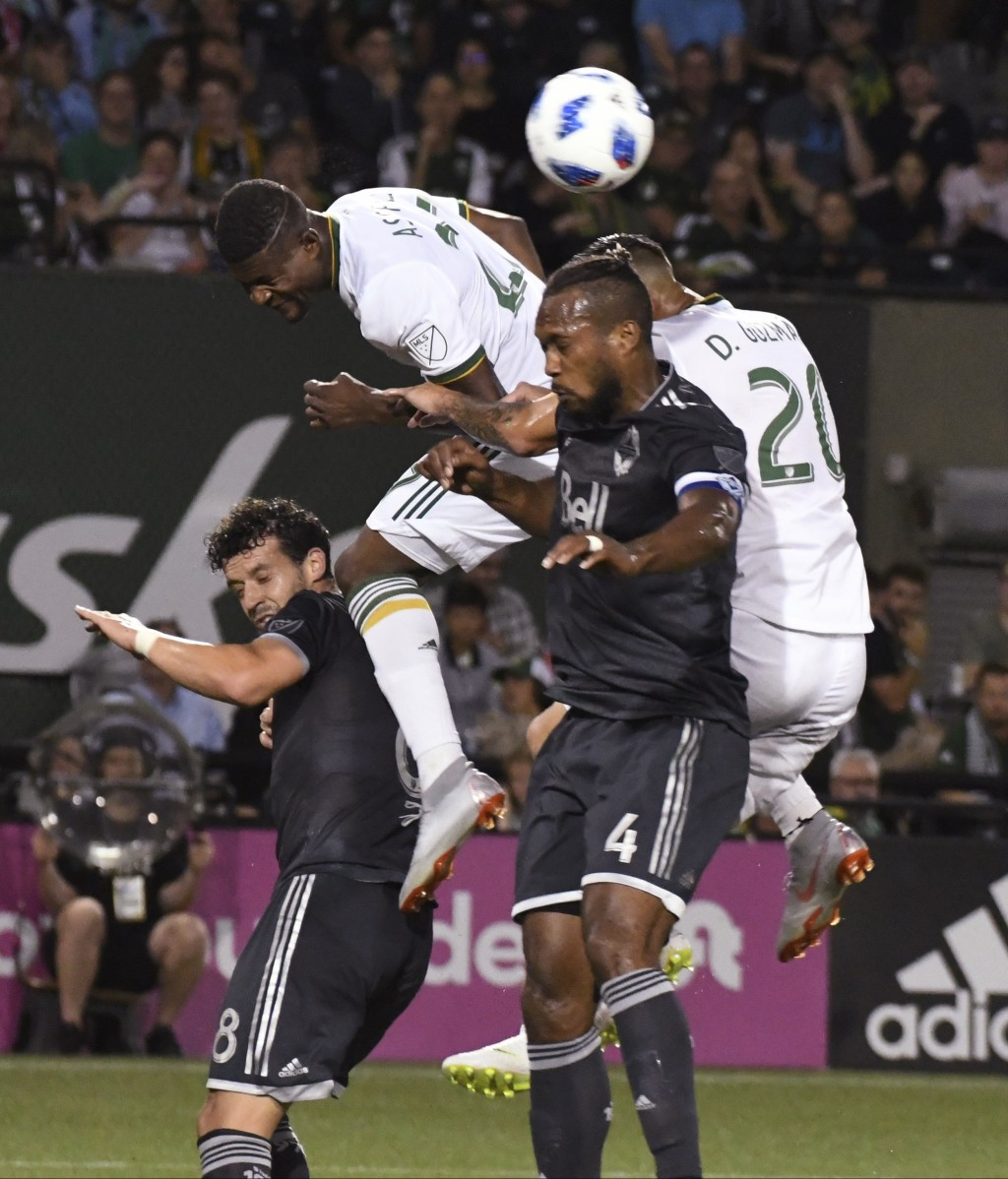 Portland Timbers' Dairon Asprilla, second from left, and David Guzman for a head ball with Vancouver Whitecaps' Kendall Waston (4) during an MLS socce