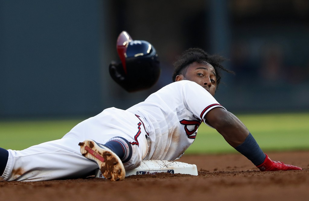 Atlanta Braves' Ozzie Albies dives into second base after a Nick Markakis fly ball in the first inning of a baseball game against the Milwaukee Brewer