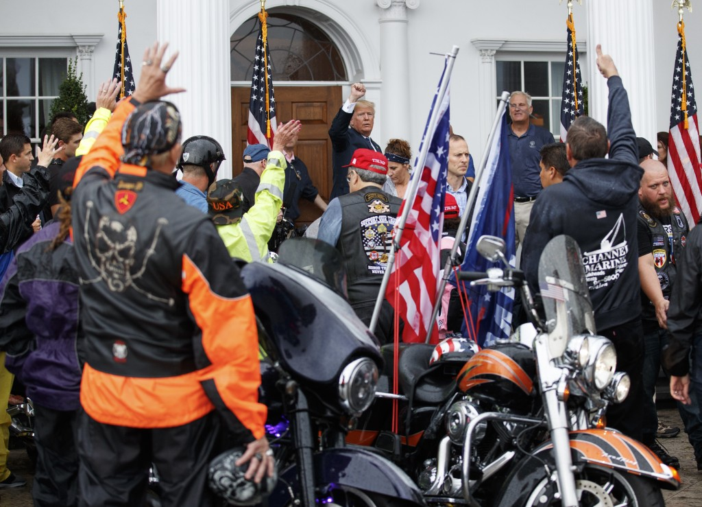 President Donald Trump gestures to cheering supporters and members of Bikers for Trump, Saturday, Aug. 11, 2018, before returning to the clubhouse of