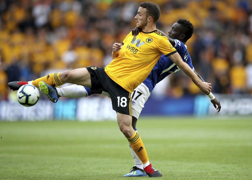 Wolverhampton Wanderers' Diogo Jota, front, and Everton's Idrissa Gueye reach for the ball during their English Premier League soccer match at Molineu