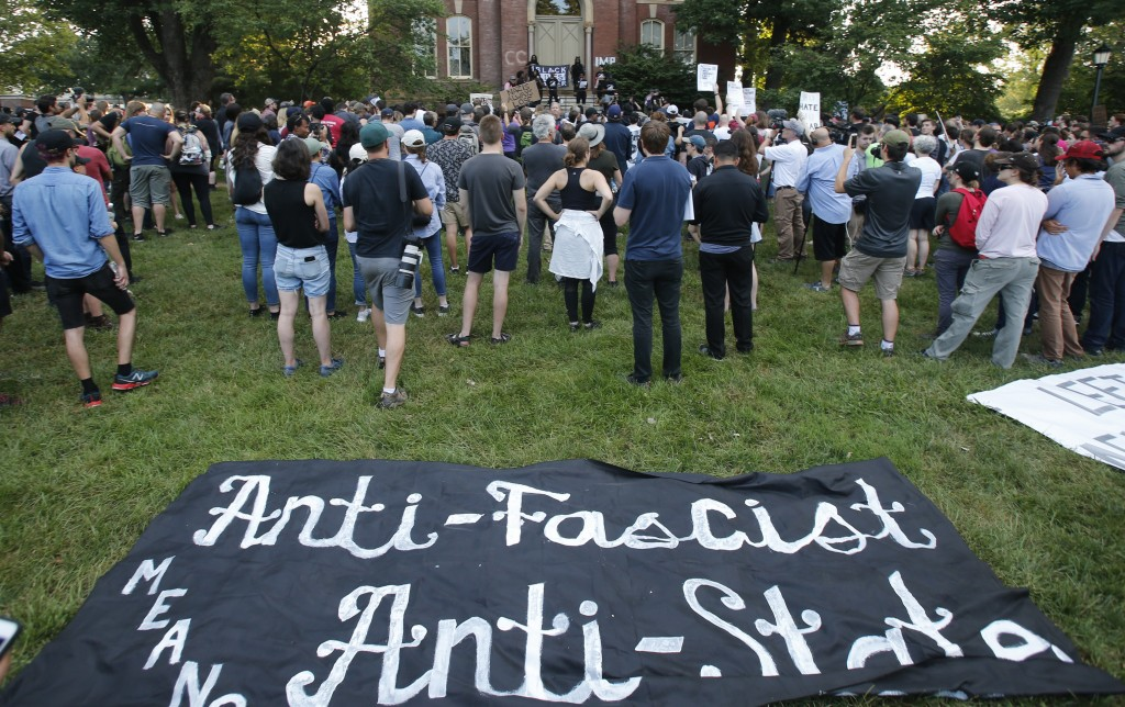 Demonstrators listen to speakers on the campus of the University of Virginia in during a rally marking the anniversary of last year's Unite the Right ...