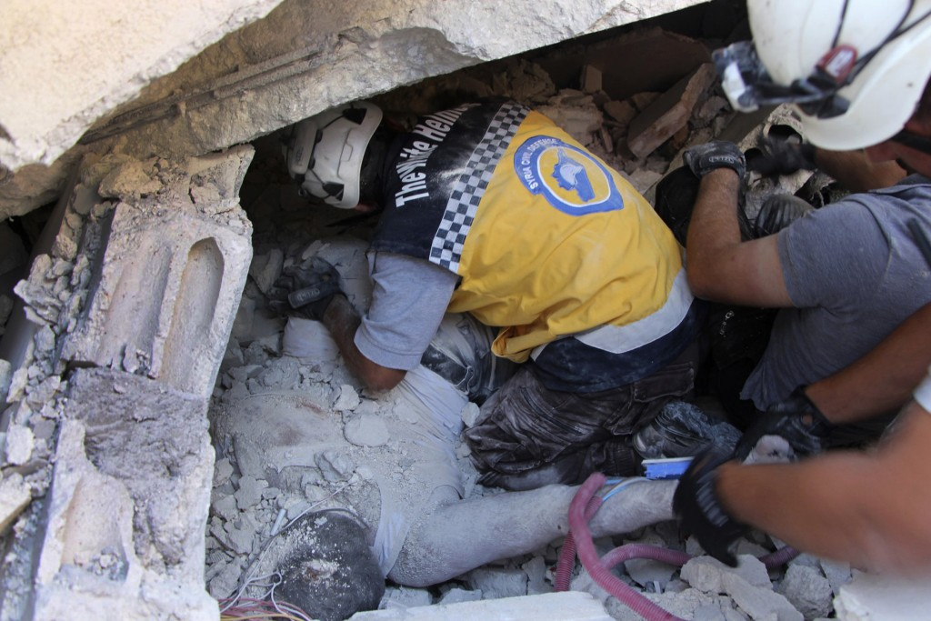 This photo provided by the Syrian Civil Defense White Helmets, which has been authenticated based on its contents and other AP reporting, shows Syrian...