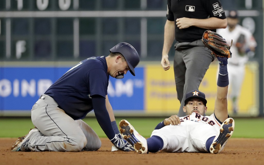 Seattle Mariners' Ryon Healy, left, reacts after being tagged out at second base as Houston Astros shortstop Carlos Correa holds the ball up in his gl