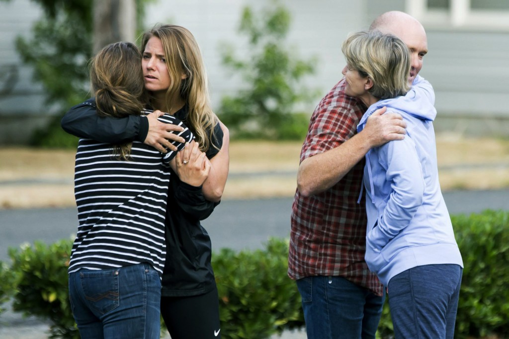 Friends of Richard Russell give parting hugs after making a statement to the media Saturday, Aug. 11, 2018, at the Orting Valley Police and Fire Depar...