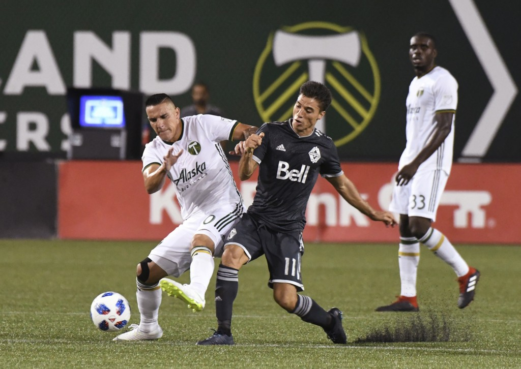 Vancouver Whitecaps' David Guzman (20) vies with Portland Timbers Nicolas Mezquida (11) for possession of the ball during an MLS soccer match Saturday