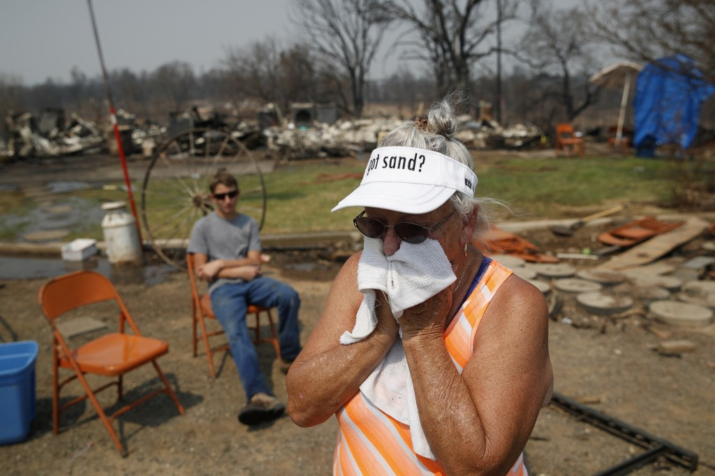 Willie Hartman cries while visiting the charred remains of her home burned in the Carr Fire, Saturday, Aug. 11, 2018, in Redding, Calif. (AP Photo/Joh