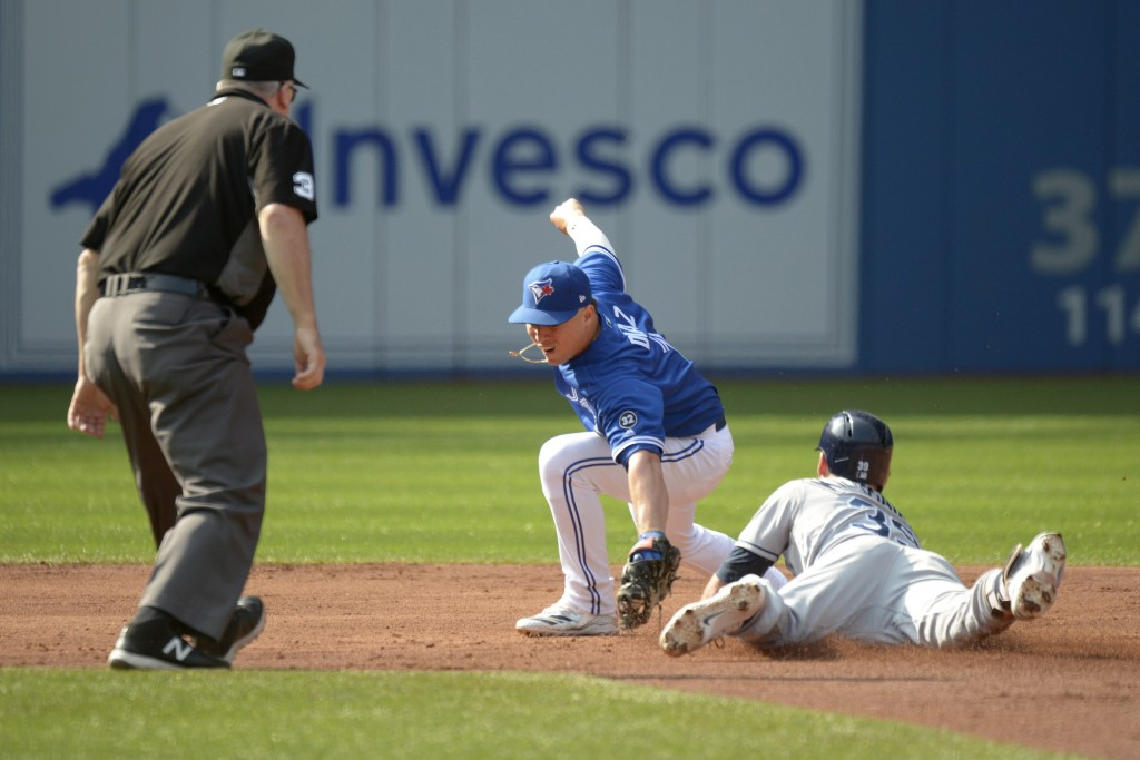 Tampa Bay Rays' Kevin Kiermaier, right, slides safely into second base ahead of the tag by Toronto Blue Jays shortstop Aledmys Diaz, center, after hit