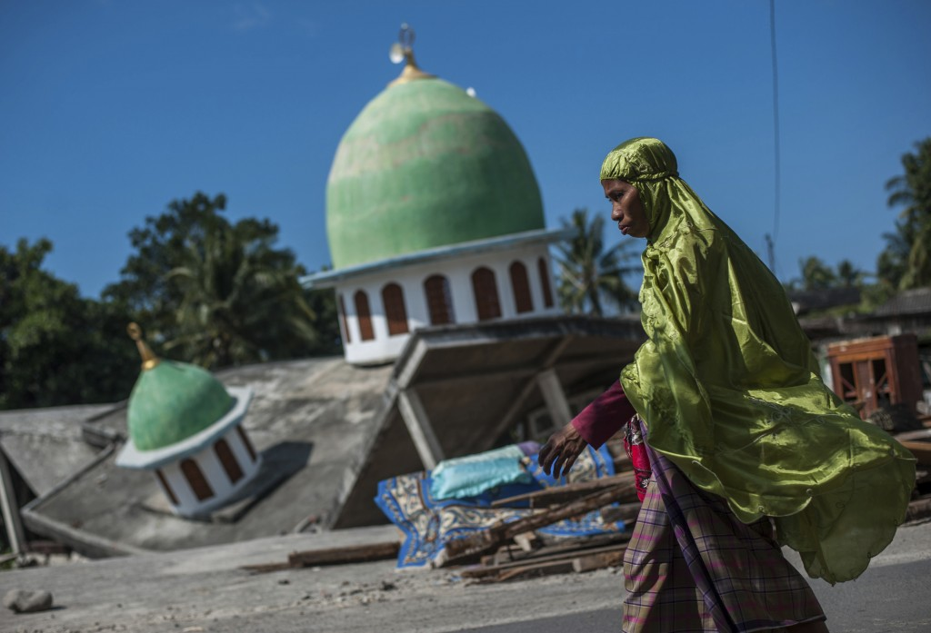 In this Saturday, Aug. 11, 2018, photo, a Muslim woman walks past a mosque collapsed during Sunday's earthquake in Gangga, Lombok Island, Indonesia. S...