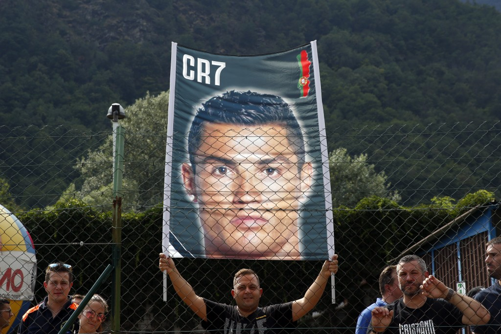 Supporters hold a banner of Cristiano Ronaldo as he arrives at Villar Perosa, northern Italy, Sunday, Aug.12, 2018, to take part in a friendly match b