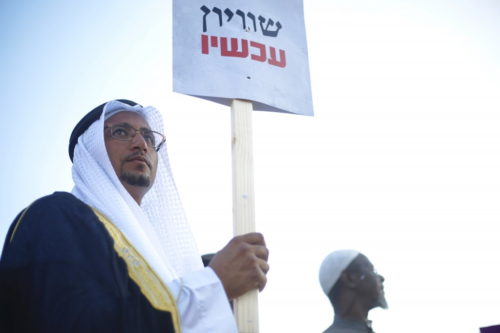 "An Arab Israeli Arab man holds a sign that reads ""Equality now"" during a protest against the Jewish nation bill in Tel Aviv, Israel, Saturday, Aug. 11"