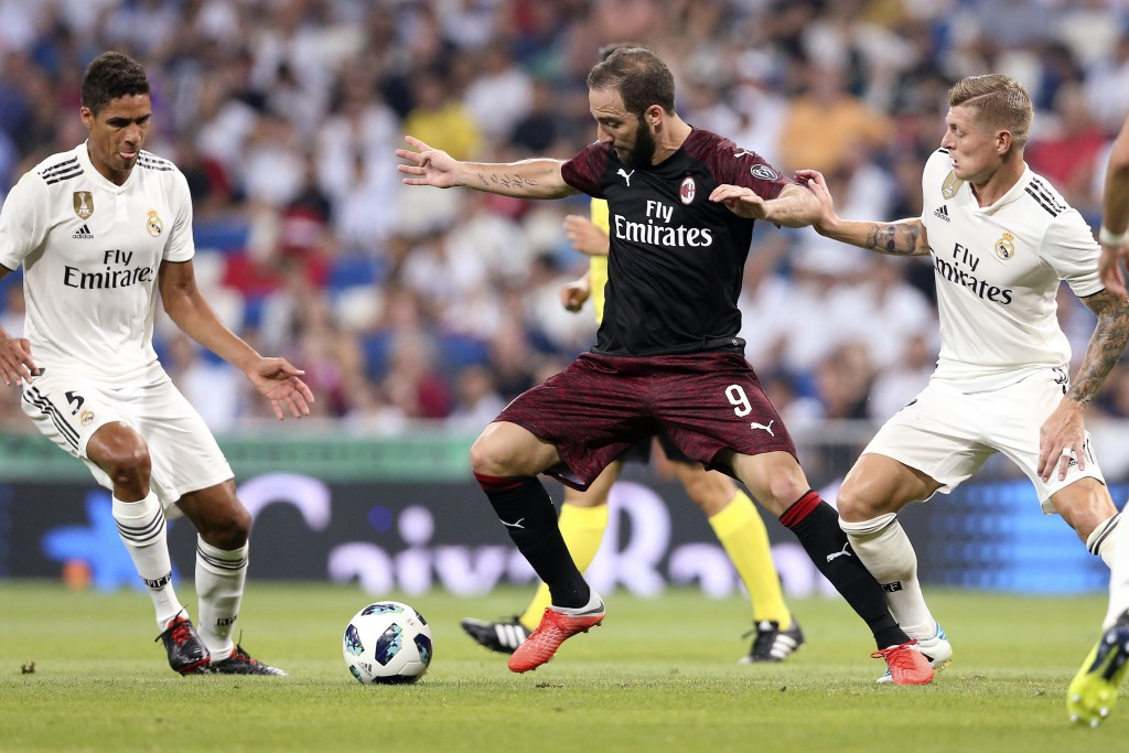 FILE - In this Saturday, Aug. 11, 2018 file photo, AC Milan's Argentine Gonzalo Higuain, center, controls the ball between Real Madrid's Raphael Varen...