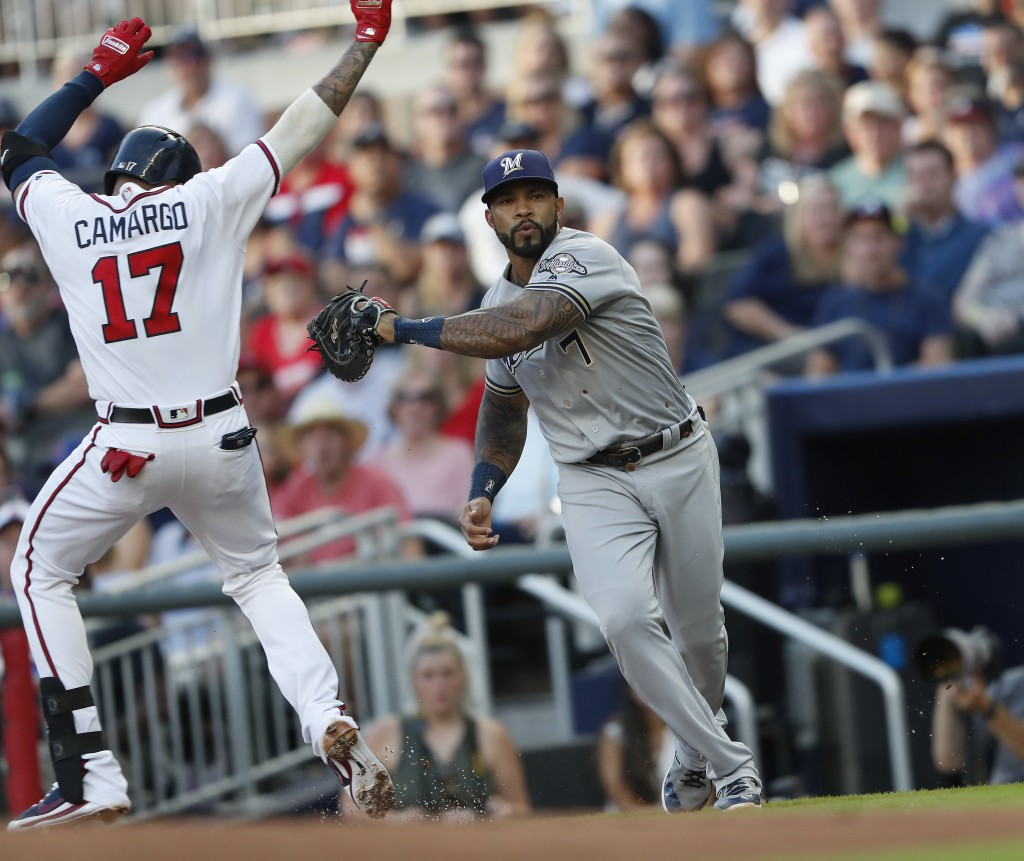 Milwaukee Brewers first baseman Eric Thames, right, tags out Atlanta Braves' Johan Camargo (17) to complete a double play in the first inning of a bas