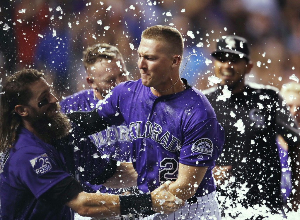 Colorado Rockies' Charlie Blackmon, left, congratulates Ryan McMahon for his three-run, walk-off home run off Los Angeles Dodgers relief pitcher JT Ch
