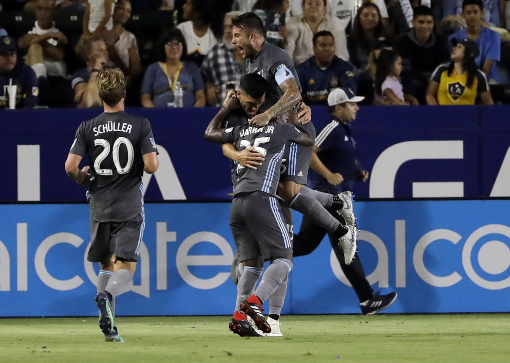 Minnesota United's Michael Boxall, center, is hugged by teammates Francisco Calvo, top right, and Carlos Darwin Quintero (25) after Boxall's goal agai...