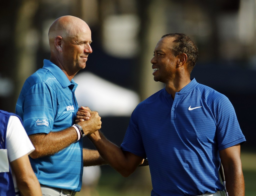 Stewart Cink, left, and Tiger Woods shake hands following the third round of the PGA Championship golf tournament at Bellerive Country Club, Saturday,