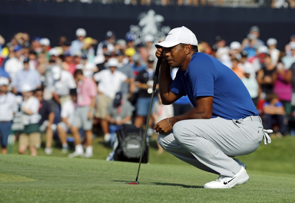 Tiger Woods looks at his putt on the 18th green during the third round of the PGA Championship golf tournament at Bellerive Country Club, Saturday, Au