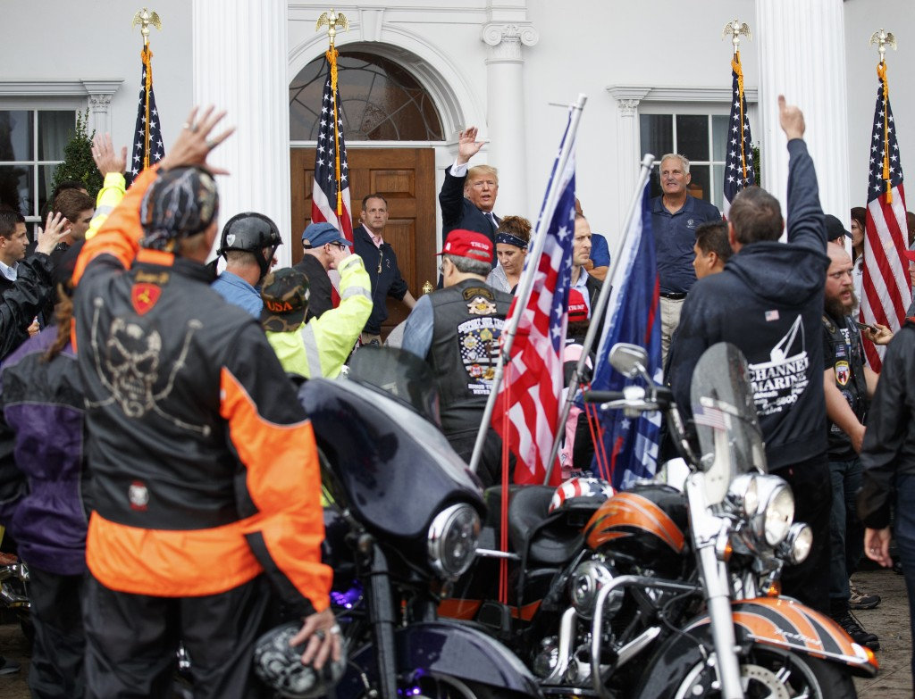 President Donald Trump waves as he is cheered by members of Bikers for Trump and supporters, Saturday, Aug. 11, 2018, at the clubhouse of Trump Nation