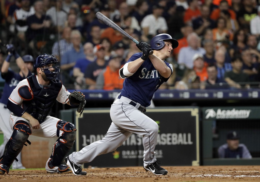 Seattle Mariners' Kyle Seager, right, hits an RBI-double as Houston Astros catcher Max Stassi watches during the fourth inning of a baseball game Satu