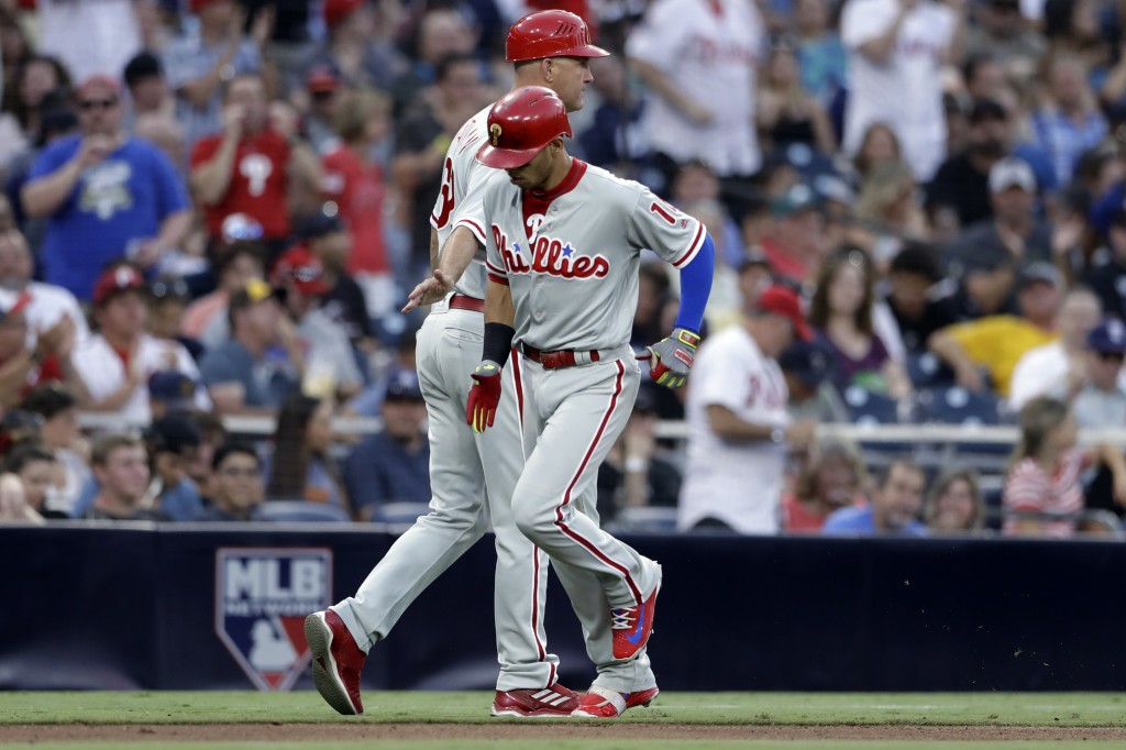 Philadelphia Phillies' Cesar Hernandez, front, is greeted by third base coach Dusty Wathan after hitting a home run during the fifth inning of a baseb
