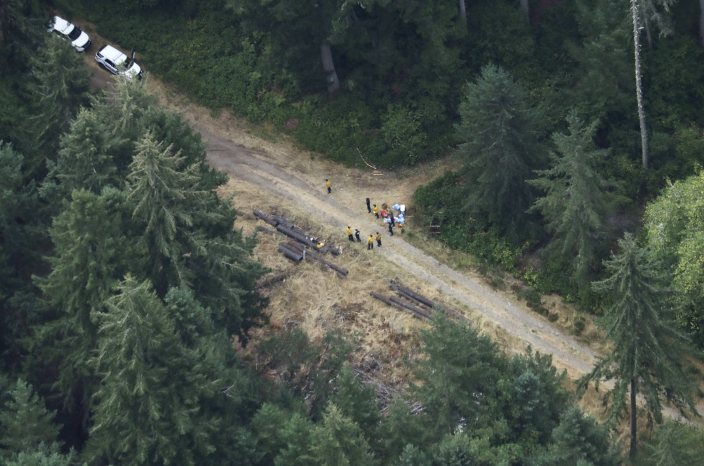 Workers gather in a staging area Saturday, Aug. 11, 2018, near Steilacoom, Wash., near the site on Ketron Island in Washington state where an Horizon ...