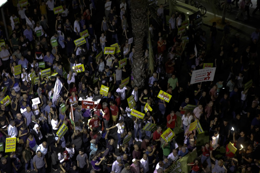 People march during a protest against the Jewish nation bill in Tel Aviv, Israel, Saturday, Aug. 11, 2018. The recently passed law that enshrines Isra