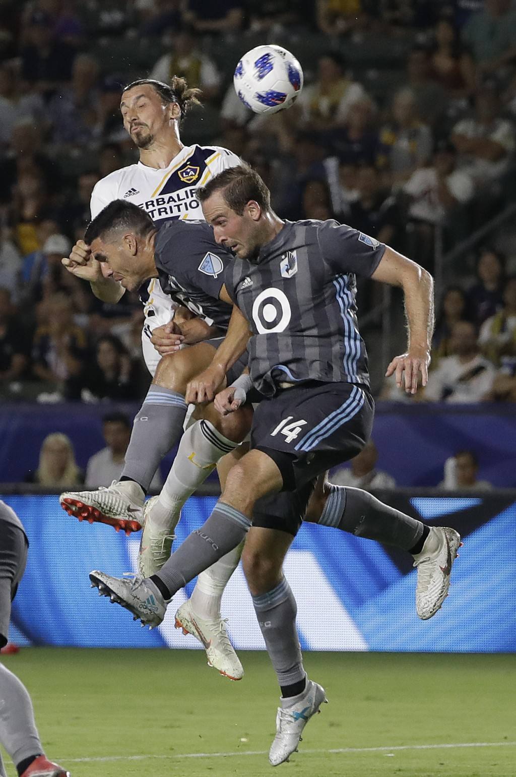 LA Galaxy forward Zlatan Ibrahimovic, top, is defended by Minnesota United's Michael Boxall, center, and Brent Kallman (14) during the second half of