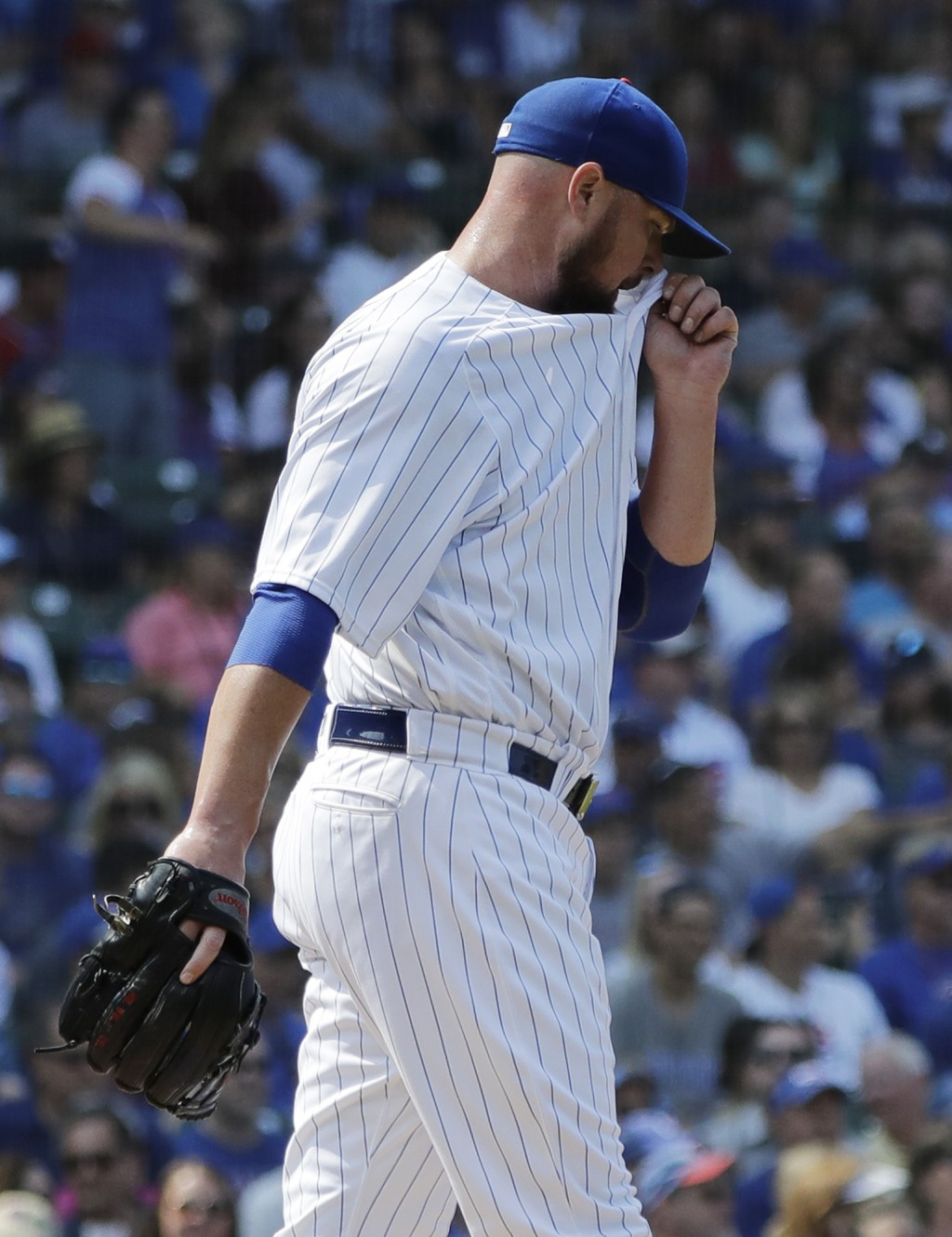 Chicago Cubs starting pitcher Jon Lester reacts as he wipes his face after Washington Nationals' Ryan Zimmerman hit a two-run home run during the firs