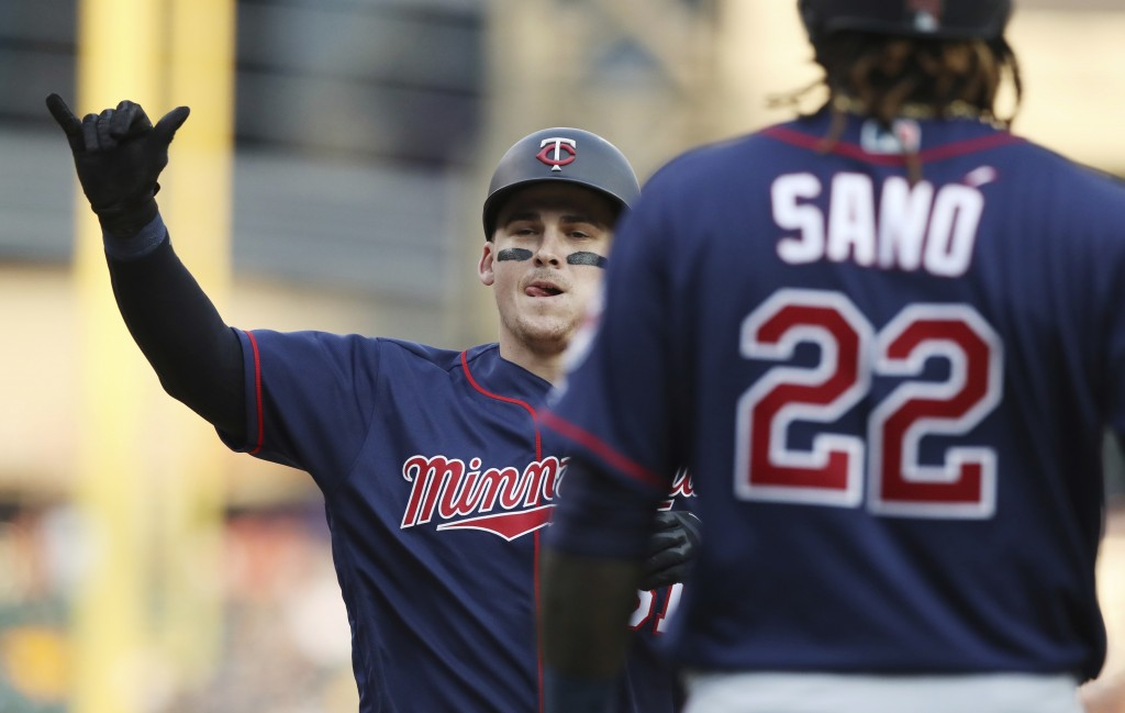 Minnesota Twins designated hitter Tyler Austin, left, approaches home plate after hitting a two-run home run that also scored Miguel Sano (22) during
