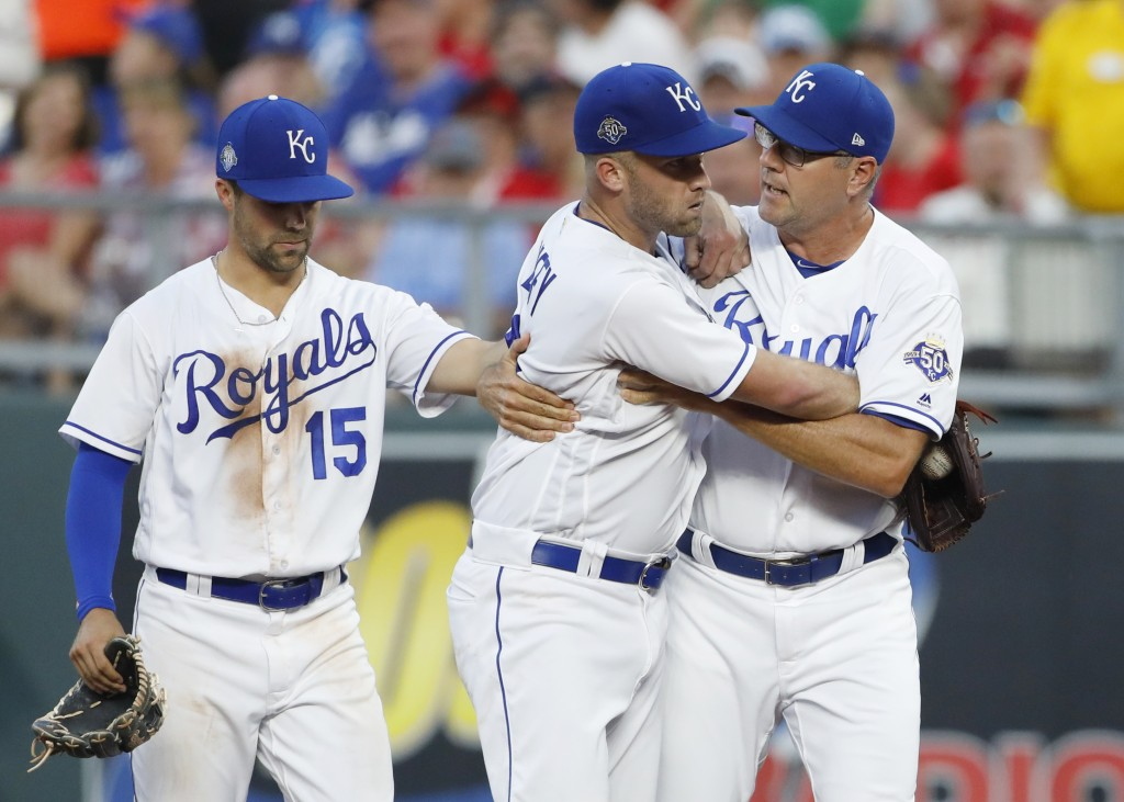 Kansas City Royals pitcher Danny Duffy, center, is held back from going after first base umpire Adam Hamari (not shown) by pitching coach Cal Eldred,