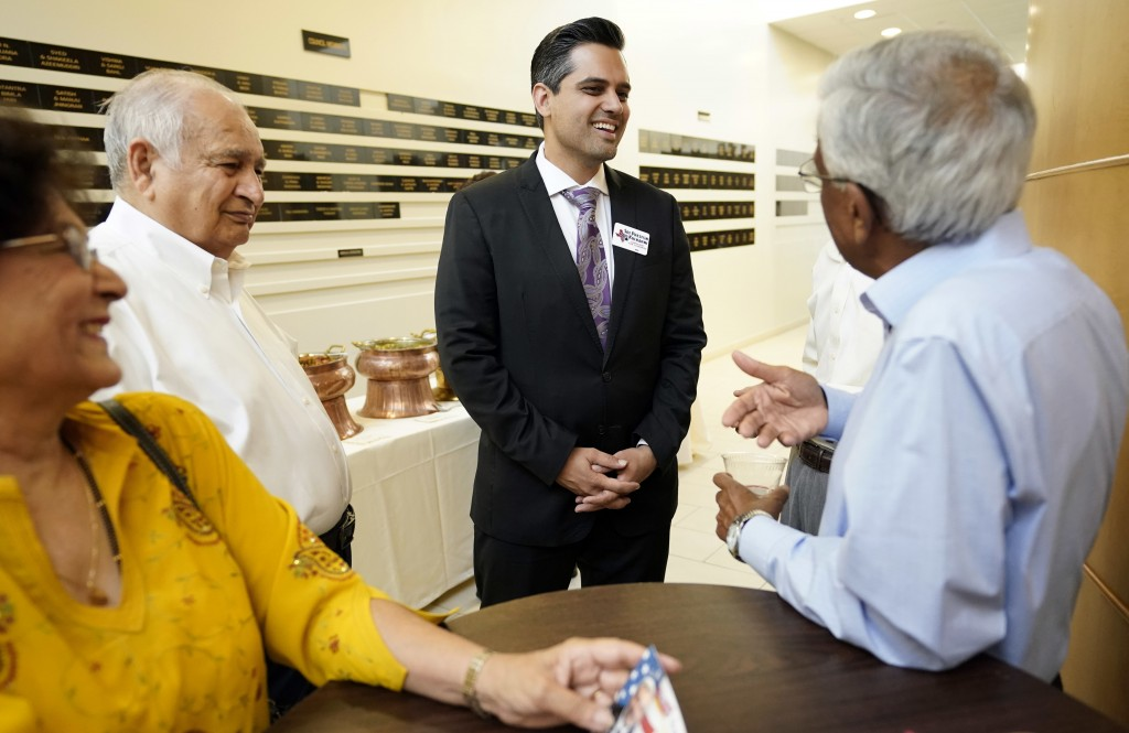 In this Sunday, July 29, 2018, photo, Democrat for Congress candidate Sri Kulkarni, center, listens to supporters attending a fundraiser for him in Ho