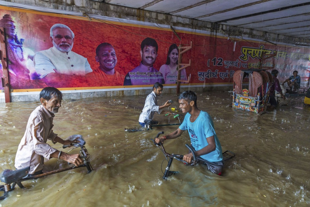 In this Sunday, Aug. 12, 2018, photo,  commuters make their way through a railway under pass where  posters of Indian Prime Minister Narendra Modi, le...