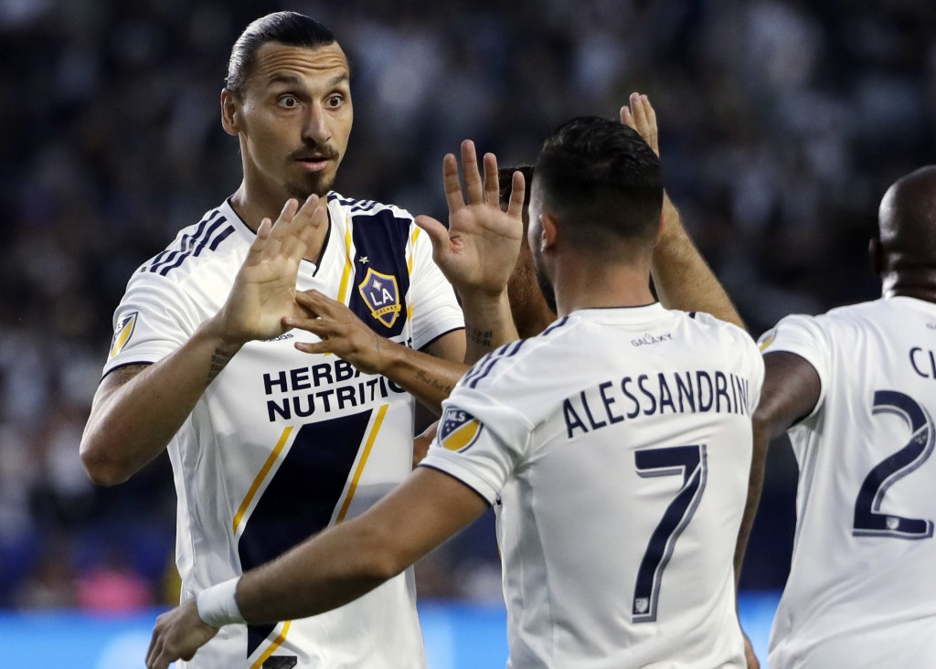 LA Galaxy midfielder Romain Alessandrini (7) celebrates his goal with teammate Zlatan Ibrahimovic during the first half of an MLS soccer match against
