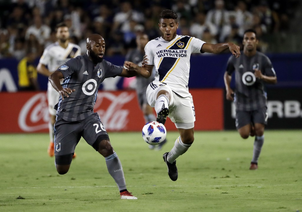 LA Galaxy midfielder Jonathan dos Santos, right, controls the ball next to Minnesota United midfielder Collen Warner during the first half of an MLS s