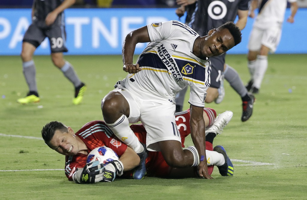 Minnesota United goalkeeper Bobby Shuttleworth, bottom, stops a shot attempt from LA Galaxy forward Ola Kamara, top, during the first half of an MLS s...