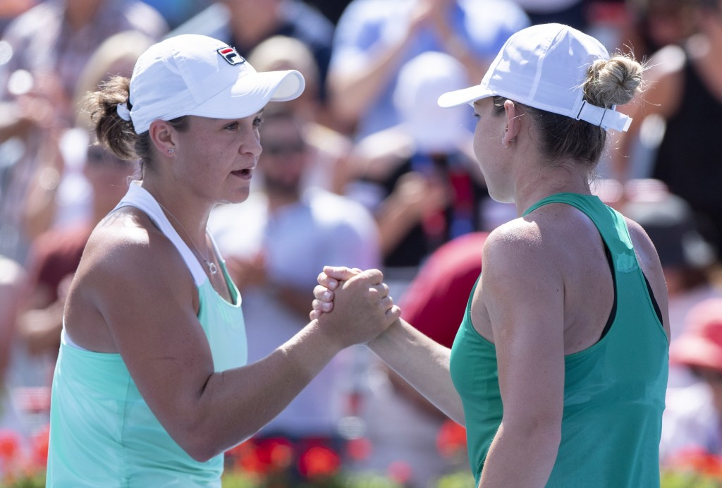 Ashleigh Barty of Australia, left, congratulates Simona Halep of Romania for her victory in semifinals play at the Rogers Cup tennis tournament Saturd