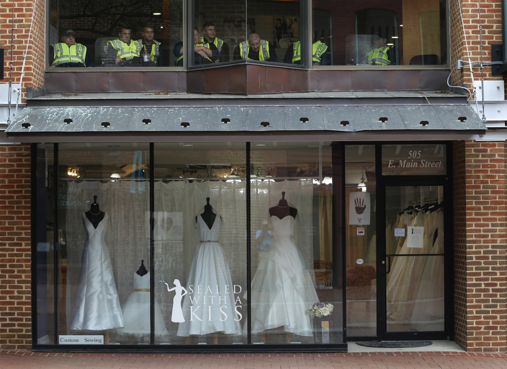 State Police take a break in an office above a closed bridal shop in the downtown area of Charlottesville, Va., Saturday, Aug. 11, 2018. Police locked