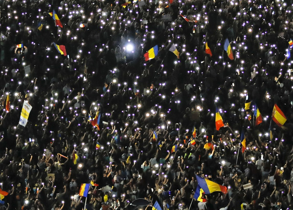 People shine the lights of their mobile phones during a protest outside the government headquarters, in Bucharest, Romania, Saturday, Aug. 11, 2018. R