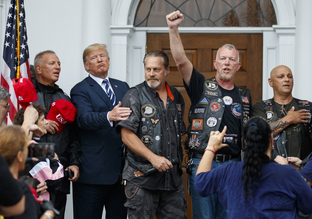 President Donald Trump stands in the rain with members of Bikers for Trump and supporters after saying the Pledge of Allegiance, Saturday, Aug. 11, 20