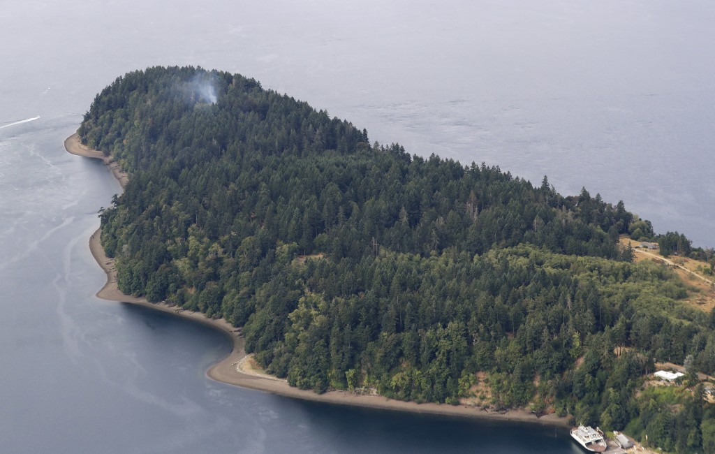 Smoke rises from the site on Ketron Island in Washington state where an Horizon Air turboprop plane crashed Friday after it was stolen from Sea-Tac In
