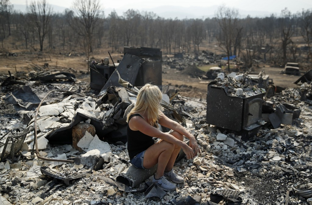 Diana Hartman sits while helping to sift through the charred remains of her mother-in-law's home that was burned in the Carr Fire, Saturday, Aug. 11,