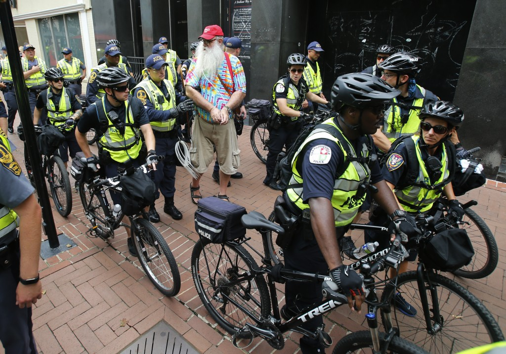 State Police escort local resident, John Miska, red hat, after he was arrested in the locked down downtown area in Charlottesville, Va., Saturday, Aug