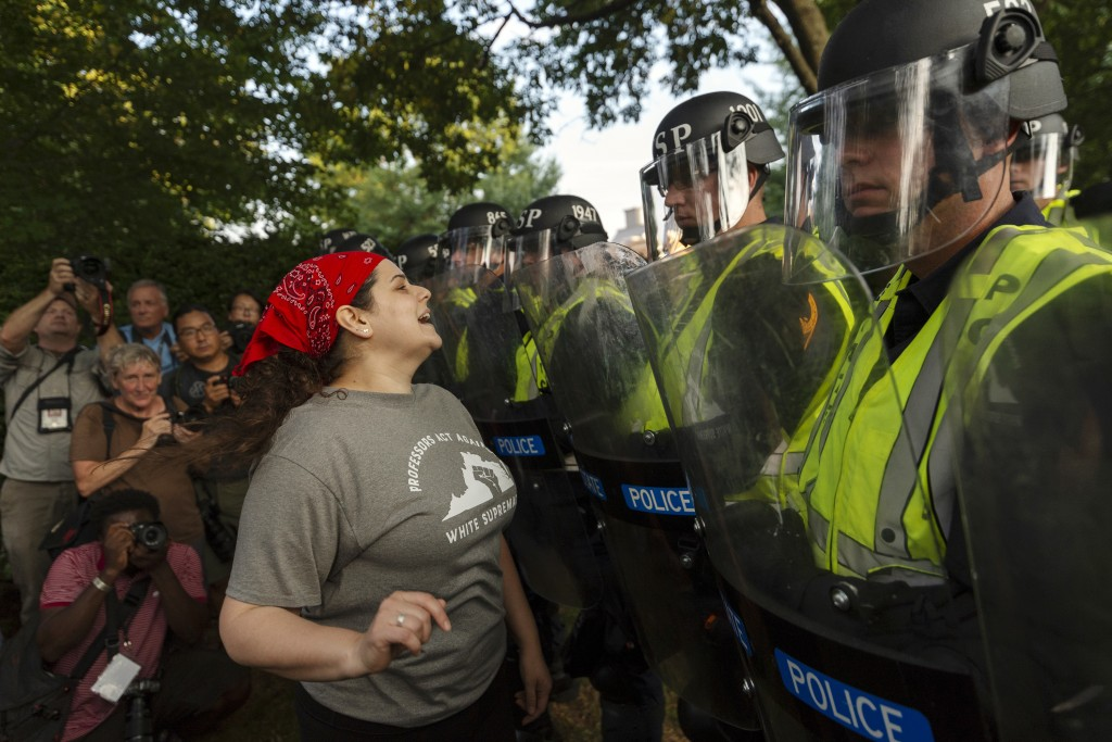 Emily Filler attempts to dissuade state police from advancing on students rallying on the grounds of the University of Virginia on the anniversary of