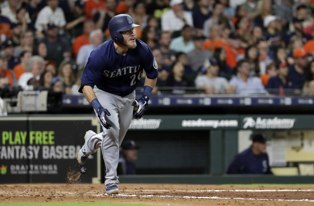Seattle Mariners' Chris Herrmann drops his bat after hitting an RBI-triple against the Houston Astros during the fourth inning of a baseball game Satu