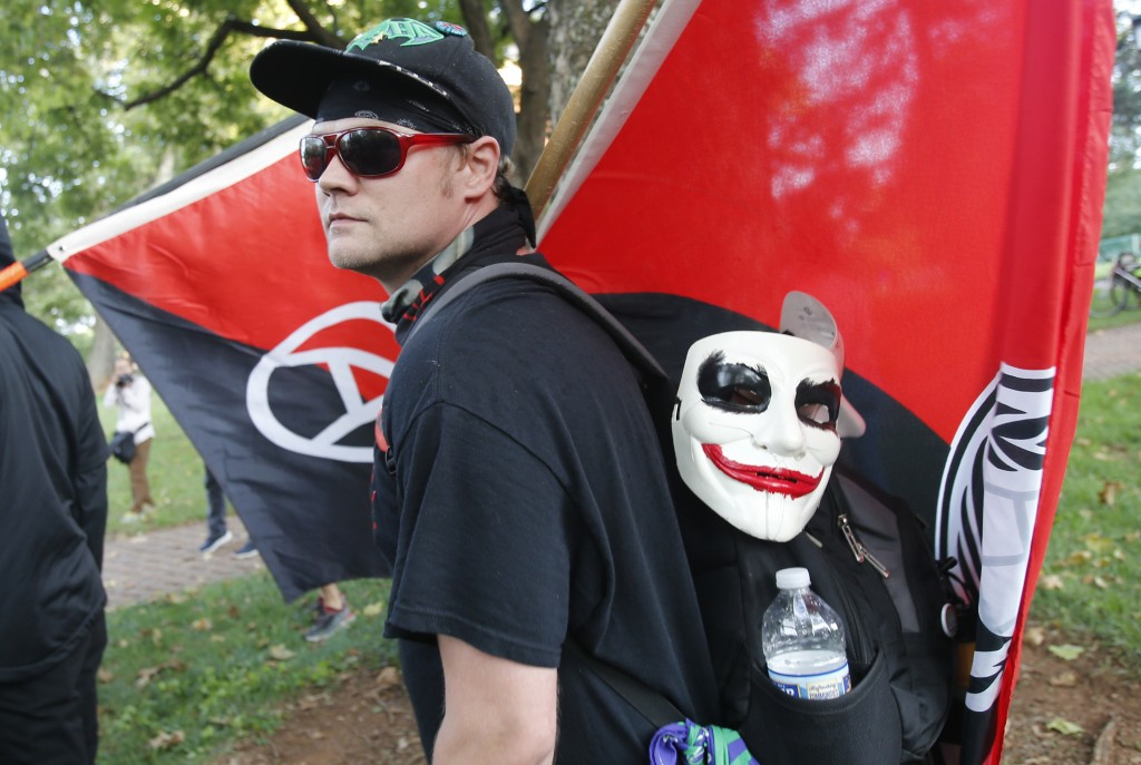 An anti-fascist demonstrator marches on the campus of the University of Virginia during a rally marking the anniversary of last year's Unite the Right...