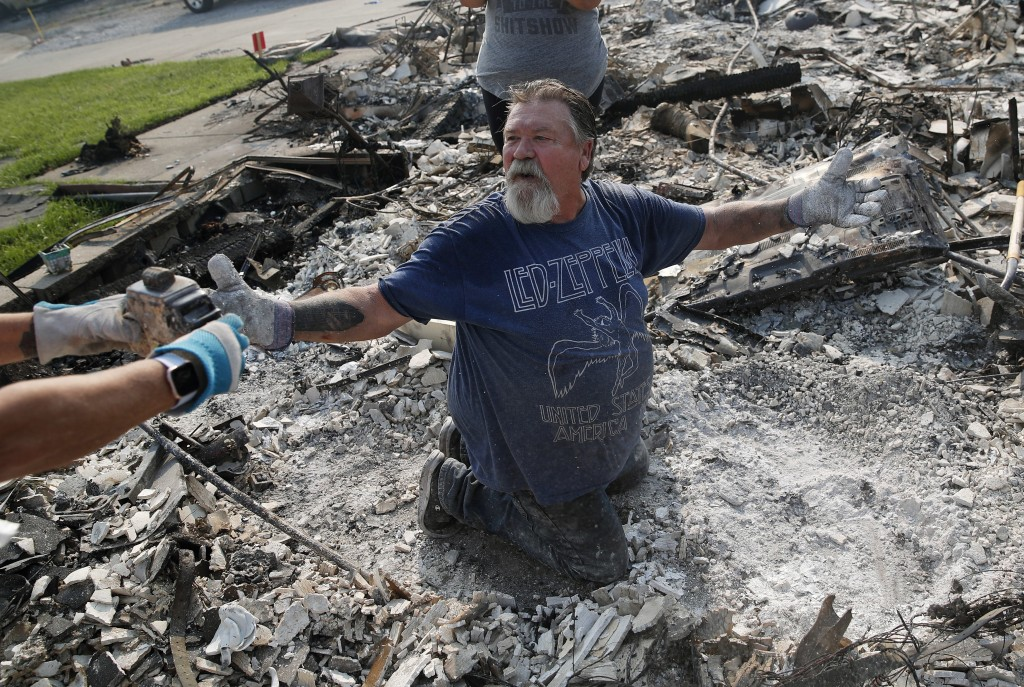 Rick Kincaid reacts as his wife Melodie Kincaid, left, finds his childhood toy as they sift through the charred remains of their home burned in the Ca