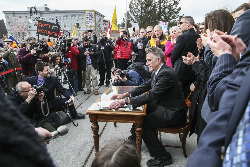 FILE - In this April 11, 2018 file photo, Vermont Gov. Phil Scott finishes signing a gun restrictions bill on the steps of the Statehouse in Montpelie